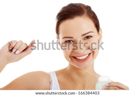 Beautiful young woman with dental floss. Isolated on white. - stock photo