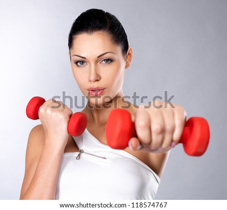 beautiful young woman with dumbbells -  grey studio background. Healthy lifestyle concept. - stock photo