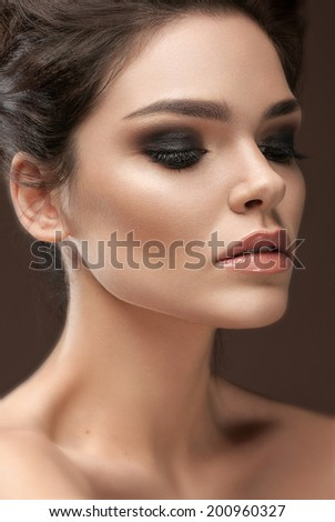 Beautiful young woman with evening make-up and volume hairstyle . Smoky eyes. Fashion photo - stock photo