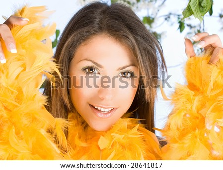 beautiful young woman with face framed in silver yellow feathers - stock photo