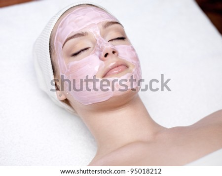 Beautiful young woman with facial mask in spa salon - indoors - stock photo