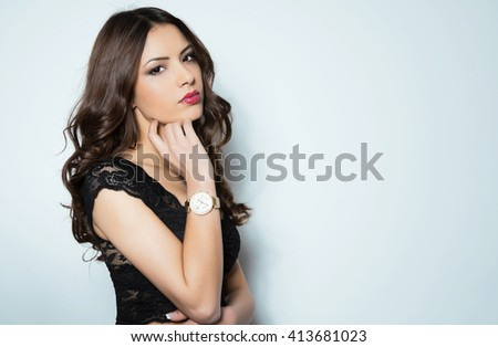 Beautiful young woman with flawless skin and perfect make-up wearing wrist watch - stock photo