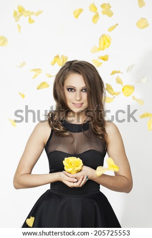 Beautiful young woman with flower and petals background - stock photo