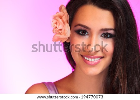 Beautiful young woman with flower on a purple background. - stock photo