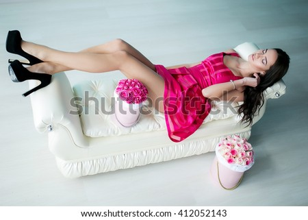 Beautiful young woman with flowers in pink dress lying on sofa, indoor portrait. - stock photo