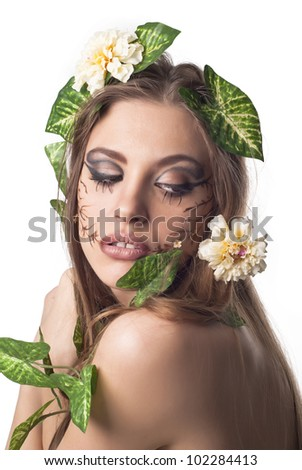 Beautiful young woman with flowers, leaves in her hair and original make up over white - stock photo