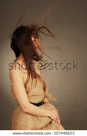 Beautiful young woman with fluttering hair and wheat ears. Nature  concept. - stock photo