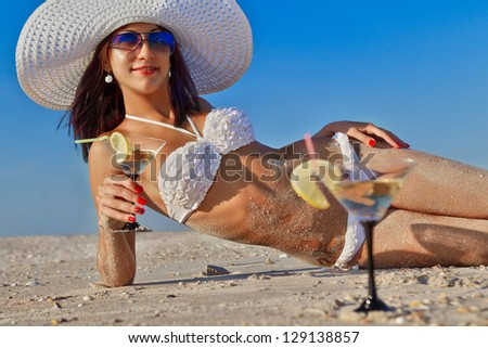 Beautiful young woman with fruit cocktail relaxing on beach - stock photo