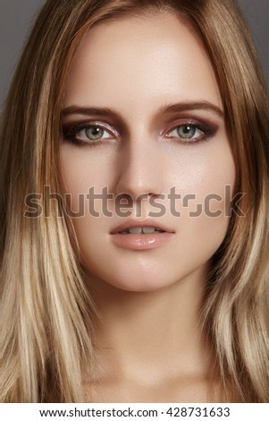 Beautiful young woman with gloss eyes and lips visage, dark blond color long hair. Beauty portrait with clean skin, glamour fashion makeup. Cosmetics, make up, hairstyle. Haircare  - stock photo