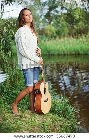Beautiful young woman with guitar on the river coast - stock photo