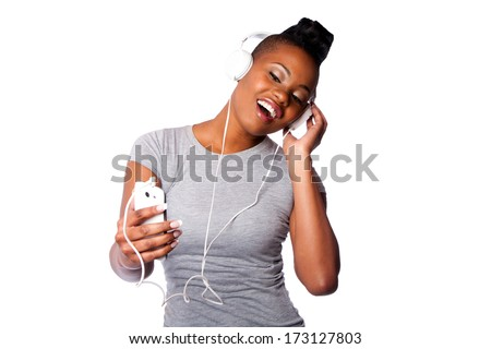 Beautiful young woman with headphones and mobile device listening grooving singing to music, isolated on white. - stock photo