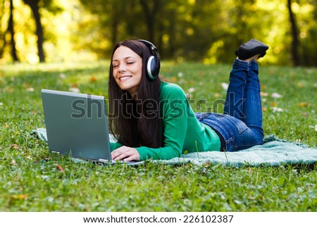Beautiful young woman with headphones enjoys in music while lying down in nature,Enjoy music - stock photo