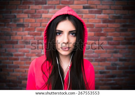 Beautiful young woman with headphones over brick wall. Looking at camera. Wearing in pink hood - stock photo