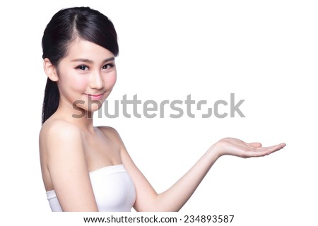 Beautiful young woman with healthy clean skin presenting something on her hand. Isolated on white. asian beauty - stock photo