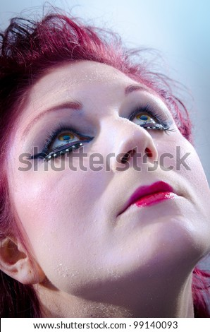 Beautiful young woman with heavy makeup looking up - stock photo