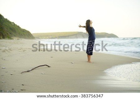 Beautiful young woman with her arms up enjoying the sense of freedom on a desolate beach. - stock photo