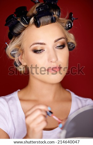 Beautiful young woman with her blond hair in curlers as she holds lipstick while looking in a mirror - stock photo