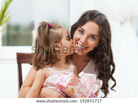 Beautiful young woman with her daughter showing love and affection. Mother's Day - stock photo