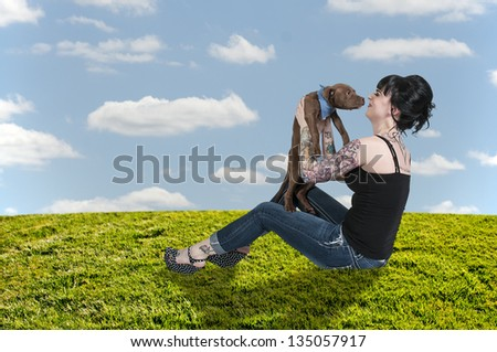 Beautiful young woman with her pit bull puppy - stock photo
