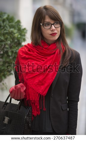 Beautiful young woman with in elegant black clothes and red scarf walking in a shopping center. - stock photo