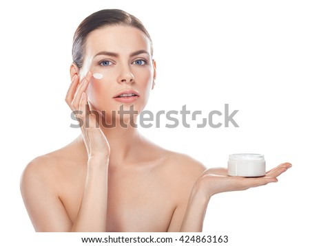 beautiful young woman with jar of cream and cosmetic cream on a cheek isolated on white with copy space - stock photo
