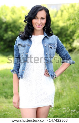 Beautiful young woman with jeans jacket in a park - stock photo