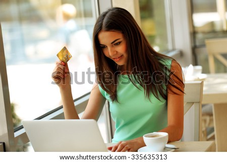 Beautiful young woman with laptop and credit card in cafe - stock photo