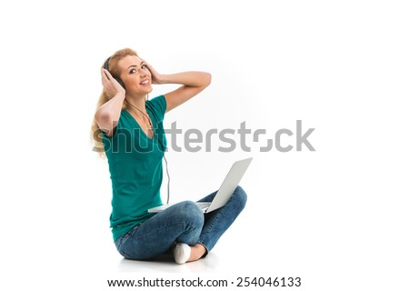 Beautiful young woman with laptop isolated on white. Positive woman using her laptop and listening to music in headset - stock photo