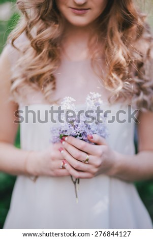 Beautiful young woman with long beautiful curly hair in a white chiffon dress posing in a garden with lilac. Spring mood - stock photo