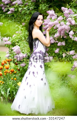Beautiful young woman with long black hair in blooming garden - stock photo