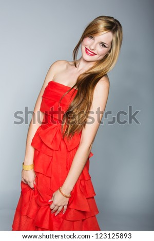 beautiful young woman with long blond hair in authentic vintage red silk dress on grey studio background - stock photo