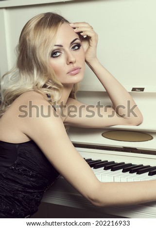 Beautiful young woman , with long blond hair , in elegant black dress , near a piano looking in camera - stock photo