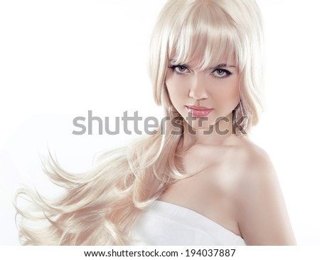 Beautiful young woman with long blond hair. Pretty model poses at studio. - stock photo