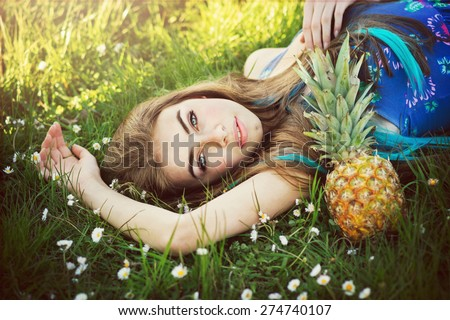 Beautiful young woman with long brown and blue hair in blue floral dress lying in field of daisies with pineapple next to her. Gorgeous boho styled girl portrait. Horizontal, retouched, vibrant color  - stock photo