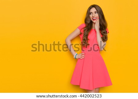 Beautiful young woman with long brown hair in pink mini dress posing with hand on chin and looking away. Three quarter length studio shot on yellow background. - stock photo