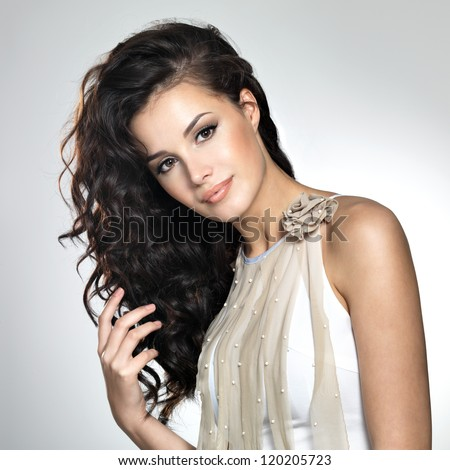 Beautiful young woman with long brown hair. Pretty model poses at studio. - stock photo