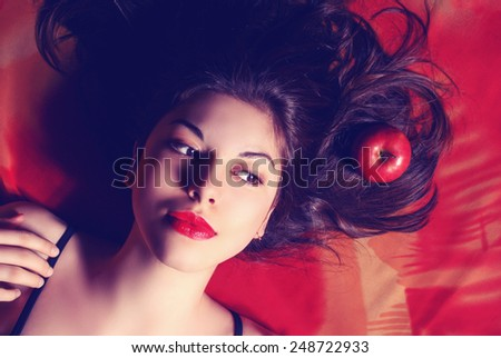 Beautiful young woman with long curly hair and bright makeup. Perfect makeup. Fashion photo - stock photo