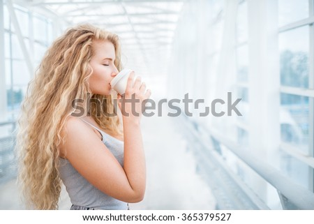 Beautiful young woman with long curly hair, holding a take away coffee cup and standing on the bridge against urban background. - stock photo