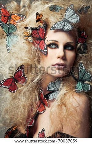 Beautiful young woman with long curly hair with butterflies. - stock photo