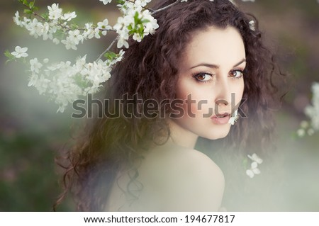 Beautiful young woman with long dark and white flowers - stock photo