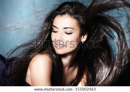 beautiful young woman with long fluttering dark hair  - stock photo