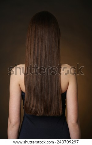 Beautiful young woman with long hair on dark brown background - stock photo