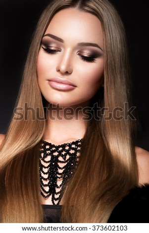 Beautiful young woman with long hair posing on black background. Healthy skin and long smooth hair. Pink lips - stock photo
