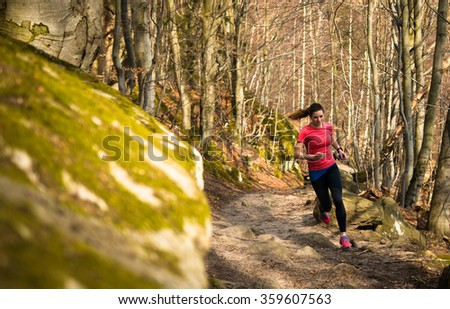beautiful young woman with long hair running on the trail in the forest with rocks - stock photo