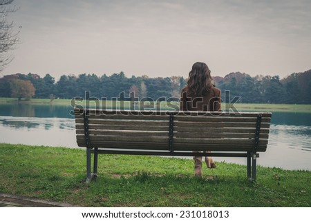 Beautiful young woman with long hair sitting on a bench in a city park - stock photo