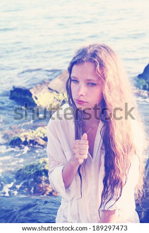 beautiful young woman with long red hair sitting on the beach - stock photo