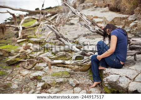 Beautiful young woman with long wet brunette hair sitting on rocks at the edge of the river - stock photo