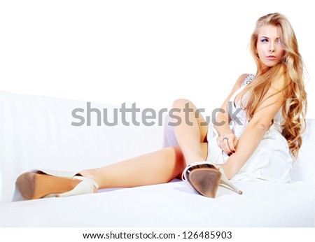 Beautiful young woman with magnificent blonde hair sitting on a sofa. Isolated over white. - stock photo
