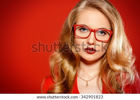 Beautiful young woman with magnificent blonde hair wearing red dress and elegant red glasses. Beauty, fashion. Optics, eyewear. Red background. - stock photo