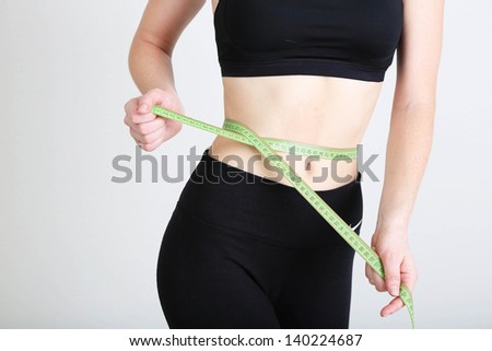 Beautiful young woman with measuring tape - stock photo